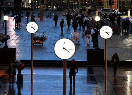 FILE PHOTO: People walk accross a plaza in London's Canary Wharf financial district