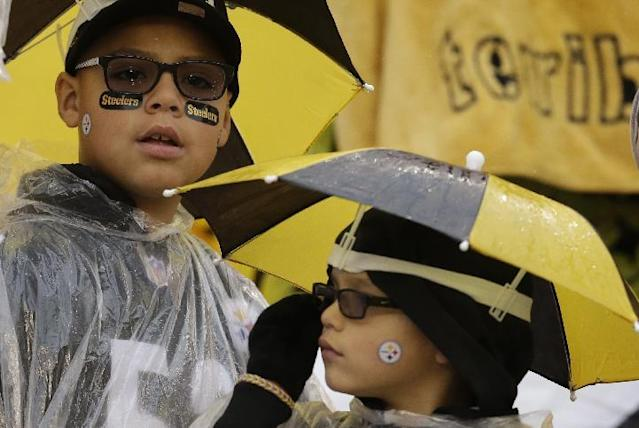 Young Pittsburgh Steelers fans wear umbrella hats as rain falls as the Steelers and the Cleveland Browns warm up before an NFL football game in Pittsburgh, Sunday, Dec. 29, 2013. (AP Photo/Gene J. Puskar)