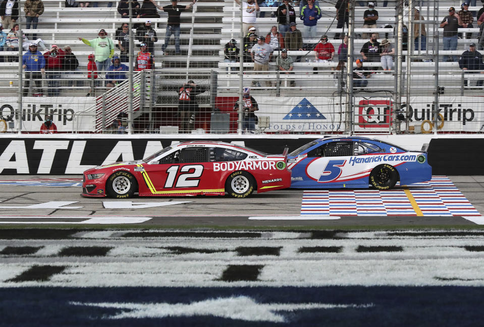 Ryan Blaney (12) passes Kyle Larson with eight laps remaining on his way to winning a NASCAR Cup Series auto race at Atlanta Motor Speedway on Sunday, March 21, 2021, in Hampton, Ga. (Curtis.Compton/Atlanta Journal-Constitution via AP)