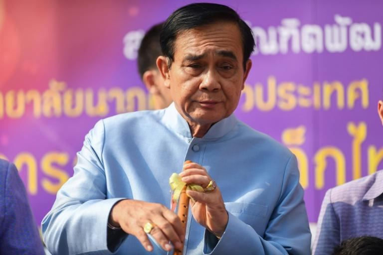 Thailand's Prime Minister Prayut Chan-O-Cha plays with a traditional flute as he arrives at the government house for a cabinet meeting on Tuesday, two days after the country's general election