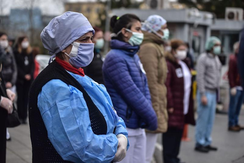 Turkish health workers join in a moment of silence in front of a hospital building in Istanbul on April 2.