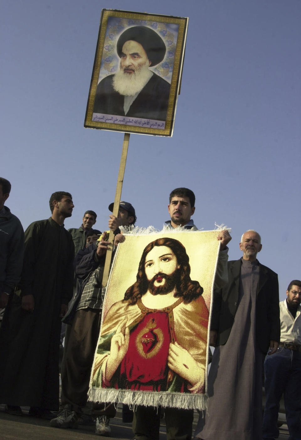 FILE - In this Jan. 19, 2004 file photo, an Iraqi Christian holds a carpet with an image of Jesus Christ and a poster of Grand Ayatollah Ali al-Husseini al-Sistani during a march in Baghdad, Iraq. On Saturday, March 6, 2021, Pope Francis will visit the 90-year-old Grand Ayatollah who is revered by many Shiites worldwide and whose words hold powerful influence in Iraq and beyond. The pontiff and ayatollah will meet in al-Sistani's modest home in the Iraqi city of Najaf. (AP Photo/Hadi Mizban, File)