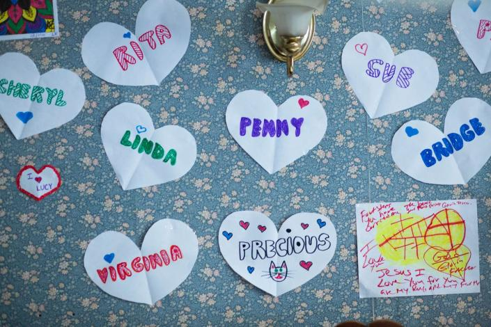 Paper hearts with women's names on them on a flowery bulletin board.