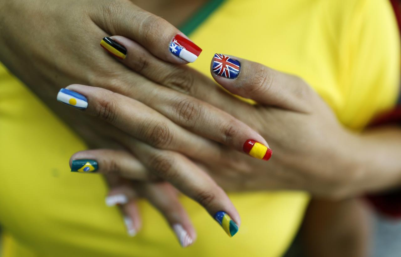 A woman shows her nails after being painted with the flags of countries that will participate in the 2014 World Cup in Rio de Janeiro May 29, 2014. The World Cup will be held in 12 cities in Brazil from June 12 till July 13. Picture taken May 29, 2014. REUTERS/Pilar Olivares (BRAZIL - Tags: SPORT SOCCER WORLD CUP SOCIETY)