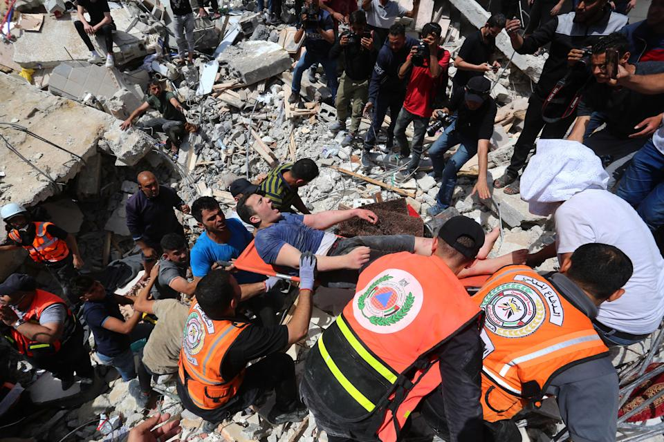 Rescue workers pull surivors from the rubble of the Abu al-Auf building (Anadolu Agency via Getty)