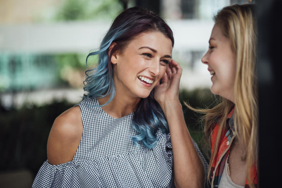 Two women are laughing and talking in the courtyard of a bar.