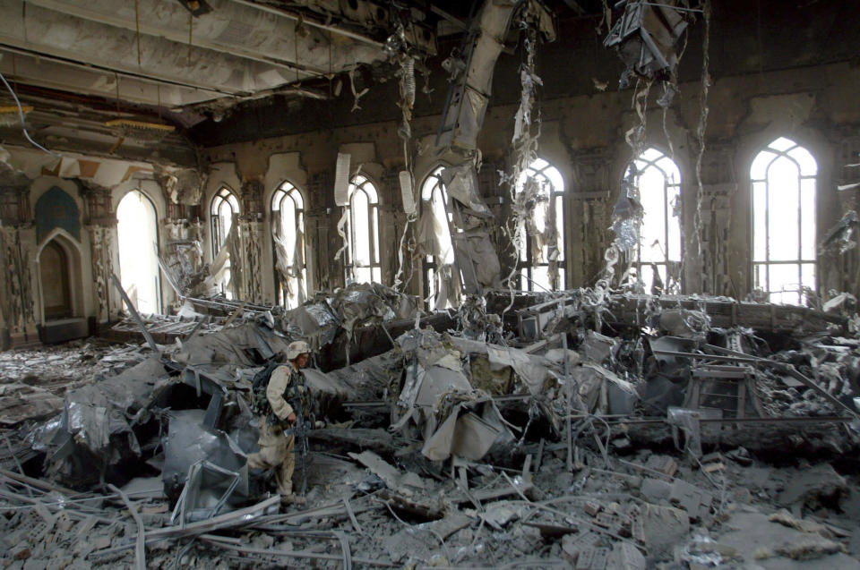 FILE - In this April 7, 2003, file photo, U.S. Army soldiers from A Company, 3rd Battalion, 7th Infantry Regiment, search one of Saddam Hussein's palaces damaged after a bombing, in Baghdad. The U.S. launched its invasion of Iraq on March 20, 2003, unleashing a war that led to an insurgency, sectarian violence and tens of thousands of deaths. (AP Photo/John Moore, File)