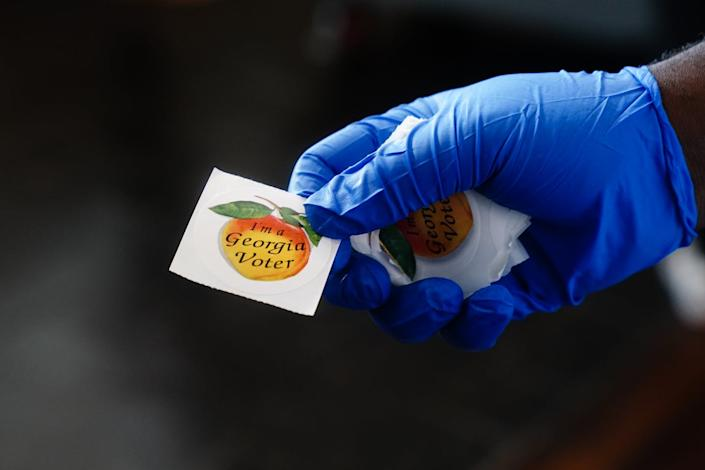 A gloved hand holding out a sticker reading 'I'm a Georgia voter.'