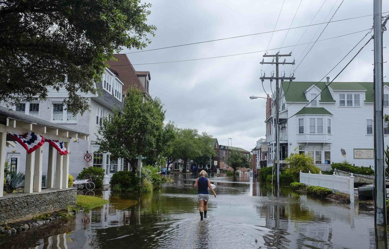 A woman walks down a flooded street after Hurricane Arthur blew through in Manteo, North Carolina July 4, 2014. The first hurricane of the Atlantic season has hit the North Carolina coast, a wet and windy spoiler of the July Fourth holiday for thousands of Americans as authorities ordered them to evacuate exposed areas. REUTERS/Chris Keane (UNITED STATES - Tags: ENVIRONMENT TPX IMAGES OF THE DAY)