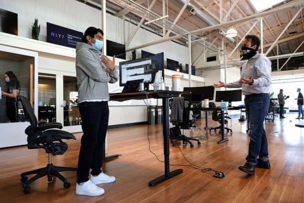 PHOTO: In this March 24, 2021, file photo, tech startup company Fast Chief Communications Officer Jason Alderman (R) talks with an employee on the first day working in the office in San Francisco. (Justin Sullivan/Getty Images, FILE)
