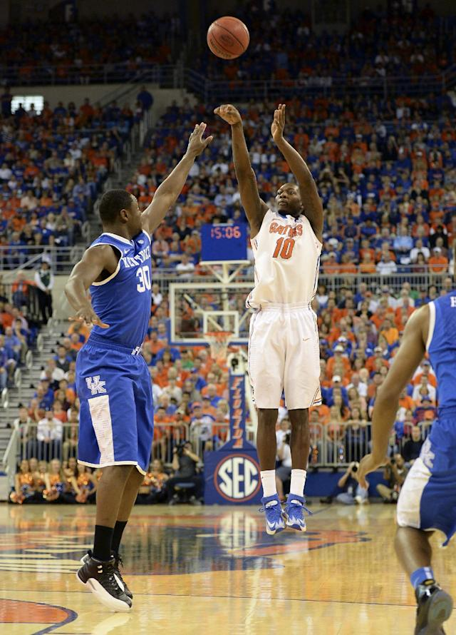 Florida forward Dorian Finney-Smith (10) shoots for 3- points as Kentucky forward Kentucky forward Julius Randle (30) defends during the first half of an NCAA college basketball game Saturday, March 8, 2014, in Gainesville, Fla. (AP Photo/Phil Sandlin)