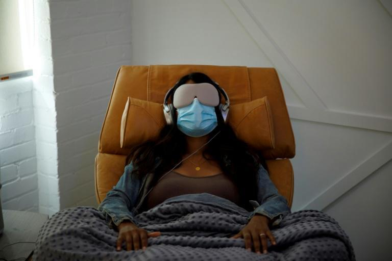 In this file photo taken on August 28, 2020, a woman demonstrates what a patient would experience in a therapy room at Field Trip, a psychedelic therapy clinic in Toronto -- psychedelics are being reconsidered as a treatment for mental health issues