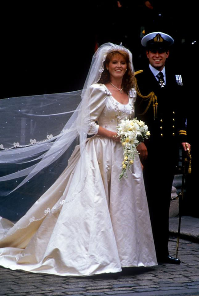 <p>Later that year, Sarah Ferguson gained a Duchess title as she wed Prince Andrew in a frothy gown by Lindka Cierach. The dress was crafted from ivory duchesse satin with various sentimental symbols sewn in. Thistles and bees represented the Ferguson's family crest while anchors and waves symbolised the Duke of York's sailing background. <em>[Photo: Getty]</em> </p>