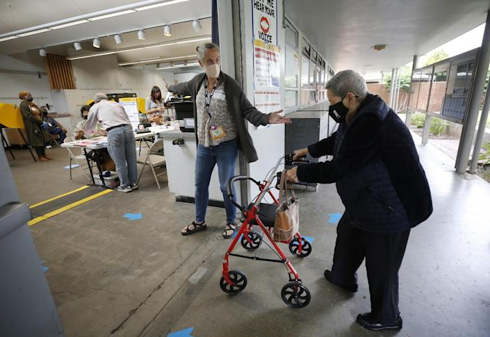 A person using a walker enters vote center