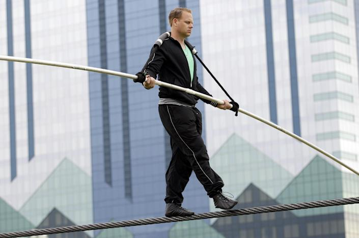FILE- In this May 16, 2012 file photo, Nik Wallenda performs a walk on a tightrope in the rain during training for his walk over Niagara Falls in Niagara Falls, N.Y. Wallenda says Monday, May 21, that ABC is adamant about making him wear the safety device out of concern for viewers who tune in to the network's three-hour, prime-time special on June 15. (AP Photo/David Duprey, File)