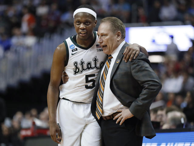 Michigan State guard Cassius Winston (5) puts his arm around coach Tom Izzo following the team's 80-63 win over LSU in an NCAA men's college basketball tournament East Region semifinal in Washington, Friday, March 29, 2019. (AP Photo/Patrick Semansky)