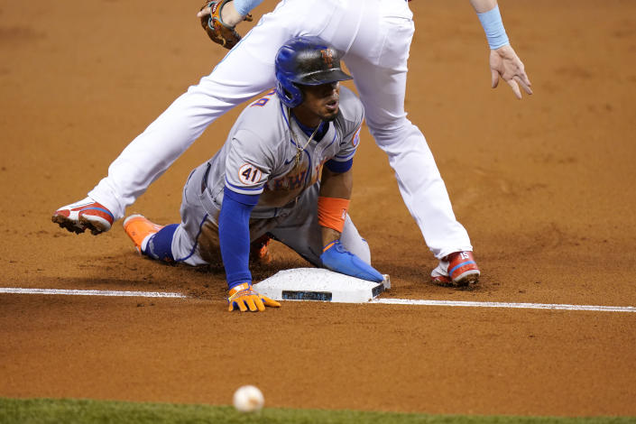 New York Mets' Francisco Lindor slides safely into third before going on to score on a throwing error by Miami Marlins center fielder Magneuris Sierra during the first inning of a baseball game Friday, May 21, 2021, in Miami. (AP Photo/Lynne Sladky)
