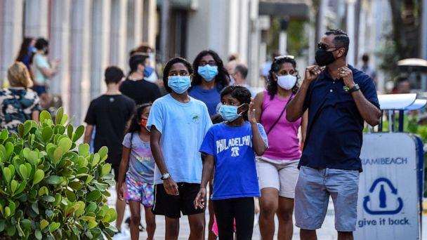 PHOTO: A family wearing facemasks walks at a shopping centre in Miami Beach, Fla., on June 29, 2020. (Chandan Khanna/AFP via Getty Images)