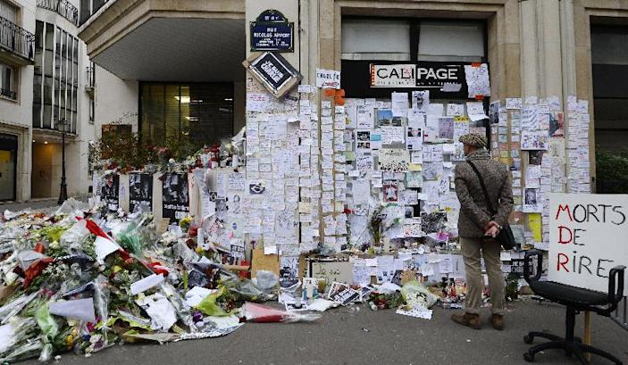 People visit a makeshift memorial near the headquarters of French satirical weekly Charlie Hebdo on January 12, 2015 in Paris, France (AFP Photo/Bertrand Guay)