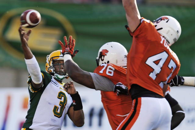 Edmonton Eskimos quarterback Steven Jyles, left, throws over the heads of B.C. Lions' Rajon Henley, centre, and James Yurichuk during the first half CFL pre-season football action in Edmonton, Alta., Thursday, June 21, 2012. THE CANADIAN PRESS/John Ulan