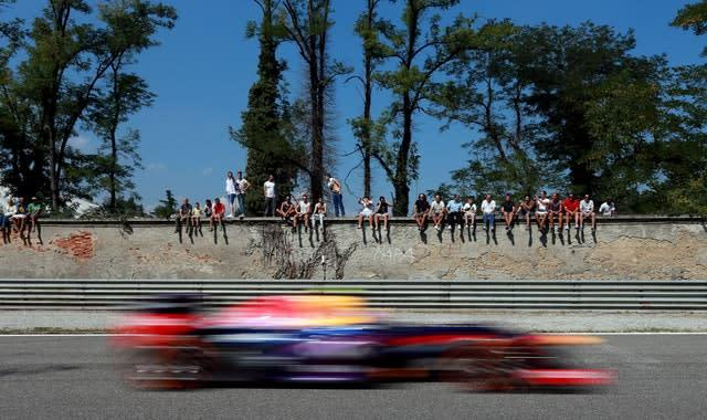 Fans sit on a wall to watch during practice day for the 2013 Italian Grand Prix in Monza. Britain's Lewis Hamilton recorded the fastest lap of the race but failed to finish on the podium, with Red Bull driver Sebastian Vettel beating Ferrari's Fernando Alonso and team-mate Mark Webber to first place (David Davies/PA)
