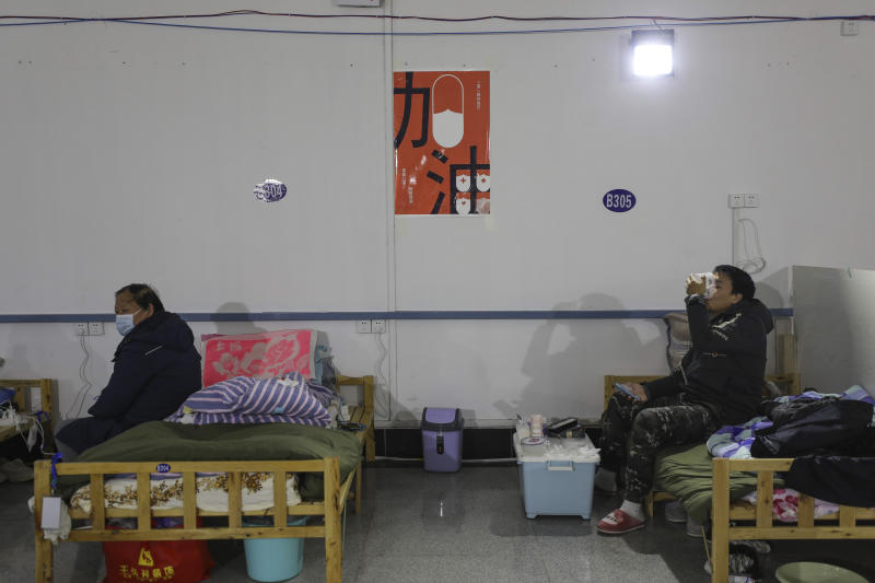 In this Friday, Feb. 21, 2020, photo, a man eats a meal at a temporary hospital at Tazihu Gymnasium in Wuhan in central China's Hubei province. China's leadership sounded a cautious note Friday about the country's progress in halting the spread of the new virus that has now killed more than 2,200 people, after several days of upbeat messages. (Chinatopix via AP)