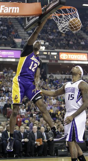 Los Angeles Lakers center Dwight Howard, left, dunks over Sacramento Kings center DeMarcus Cousins during the first quarter of an NBA basketball game in Sacramento, Calif., Saturday, March 30, 2013. (AP Photo/Rich Pedroncelli)