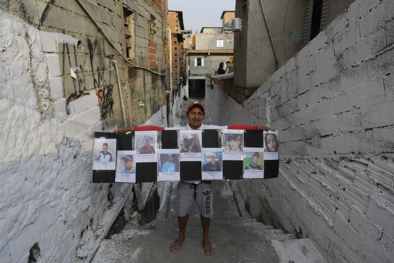 A friend holds a poster that shows images of the nine people who died in a stampede, while standing on the narrow street where they died, in Sao Paulo, Brazil, Wednesday, Dec. 4, 2019. The state's security agency said police were carrying out an operation when they were attacked by two men on a motorcycle and officers gave chase amid gunfire on sunday. The suspects fled into the street party attended by thousands of people in the Paraisopolis district. (AP Photo/Nelson Antoine)