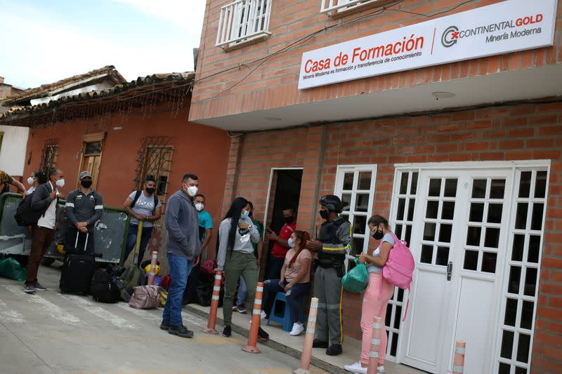 People line up in front of the formation house of the Zijin mine in Buritica