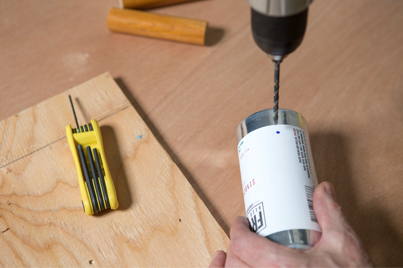 "<p>Use the cordless drill and an 11/64"" bit to drill two holes, perpendicular to each other, through the center of the can.</p>"