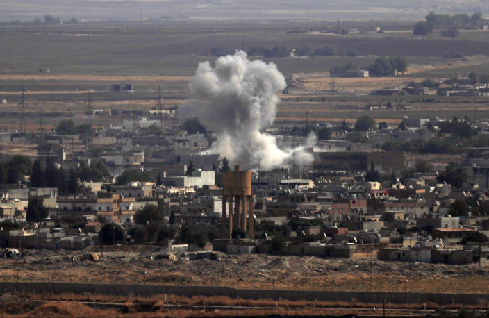 In this photo taken from the Turkish side of the border between Turkey and Syria, in Ceylanpinar, Sanliurfa province, southeastern Turkey, smoke and dust billows from targets in Ras al-Ayn, Syria, caused by bombardment by Turkish forces, Tuesday, Oct. 15, 2019. Turkish artillery on Tuesday pounded suspected Syrian Kurdish positions near the town in northeast Syria amid reports that Kurdish fighters had retaken the town as Turkey pressed ahead with a military incursion that has drawn widespread condemnation. (AP Photo/Lefteris Pitarakis)