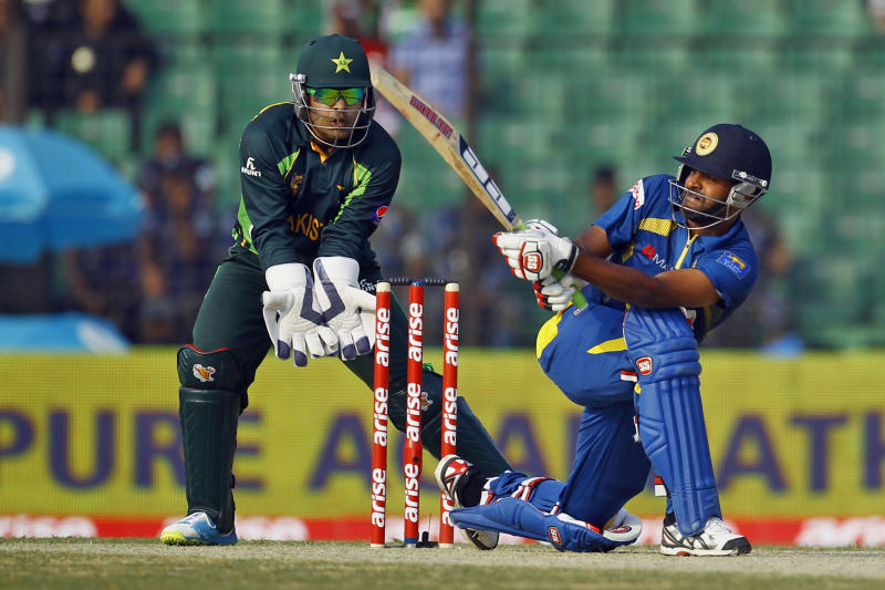 Sri Lanka's Lahiru Thirimanne, right, plays a shot, as Pakistan's wicketkeeper Umar Akmal watches during the opening match of the Asia Cup one-day international cricket tournament between them in Fatullah, near Dhaka, Bangladesh, Tuesday, Feb. 25, 2014. (AP Photo/A.M. Ahad)
