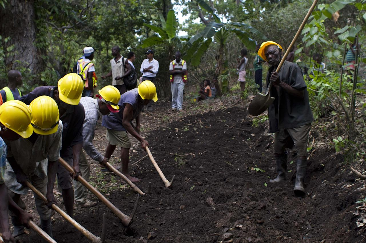 In this April 10, 2012 photo, Genove Valcimon 70, right, plays music using his shovel as laborers work to his rhythm as they build a road that will lead to an exploratory drill site in the department of Trou Du Nord, Haiti. Haiti's land may yet hold the solution to centuries of poverty: there is gold hidden in its hills, and silver and copper too. Now, two mining companies are drilling around the clock to determine how to get those metals out, and how much it might cost. (AP Photo/Dieu Nalio Chery)