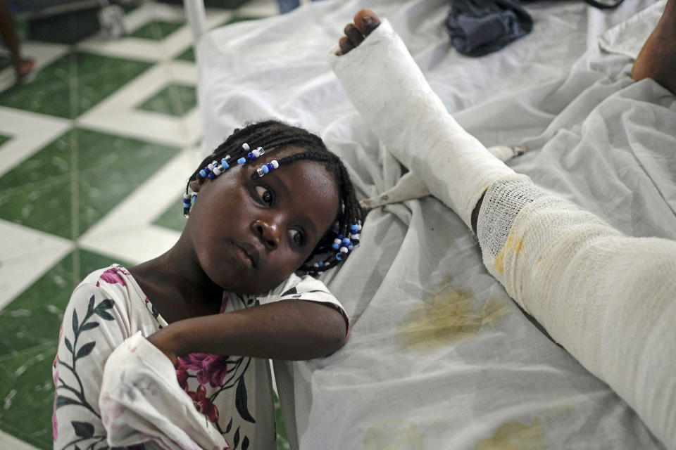 Younaika rests next to her mother Jertha Ylet, who was injured in the earthquake one week prior, at the Immaculate Conception Hospital, also known as the General Hospital of Les Cayes, Haiti, Sunday, Aug. 22, 2021. The 7.2 magnitude quake brought down their house in Camp-Perrin, killing Ylet's father and two other relatives and seriously injuring her brother. (AP Photo/Matias Delacroix)
