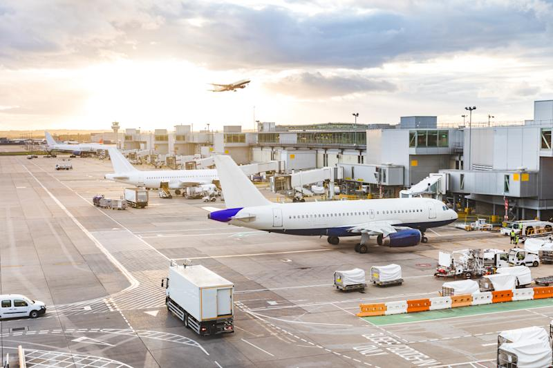 A busy airport scene showing luggage carts, delivery trucks, and planes parked and taking off.