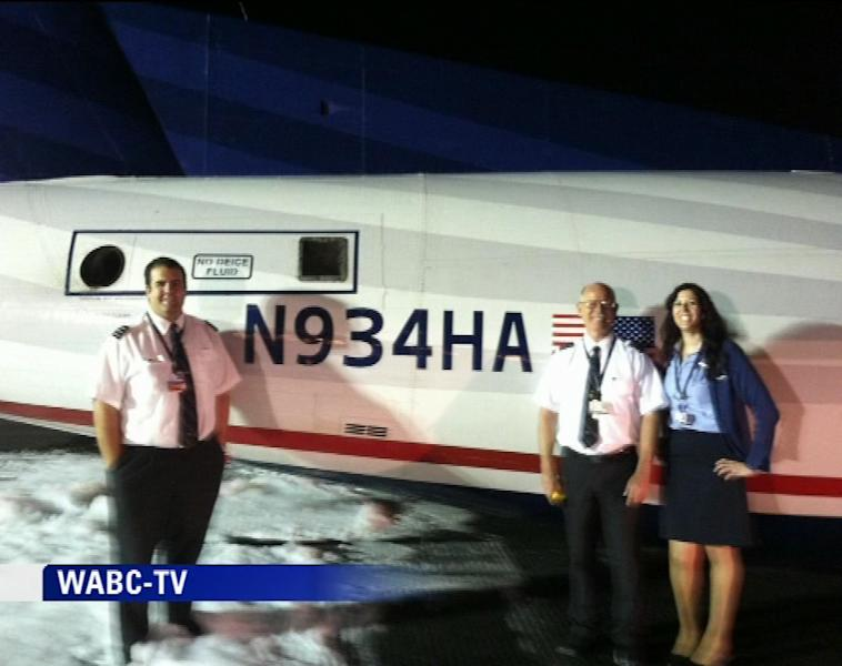 In this image taken from video and provided to WABC TV News by an airport source, pilot Edward Powers, left, poses in front of his damaged aircraft along with his crew after their US Airways Express commuter plane made a successful belly landing at Newark Liberty International Airport, Saturday, May 18, 2013. The turboprop plane reportedly left Philadelphia shortly before 11 p.m., Friday, and landed safely at Newark with its landing gear retracted at about 1 a.m., Saturday. There were no injuries. (AP Photo/WABC TV News) MANDATORY CREDIT