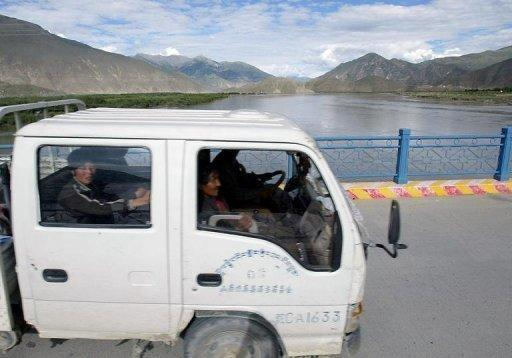 """Tibetan workers cross a bridge over the Yarlung Tsangpo river in China's southwestern Tibet region, which is known as the Brahmaputra River downstream in India. Water levels of the major river in India's northeast are """"normal,"""" an Indian government official said Friday, denying claims a dam in neighbouring China had caused them to plunge"""