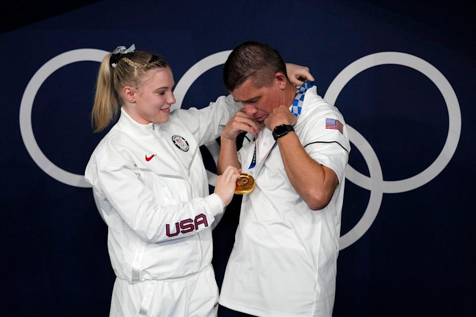 Jade Carey places her gold medal around her father's neck.