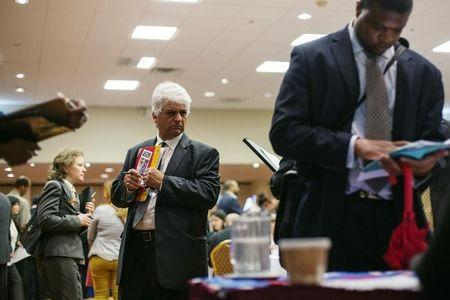 A man walks past job seekers as they fill out job applications for recruiters during a job fair in New York