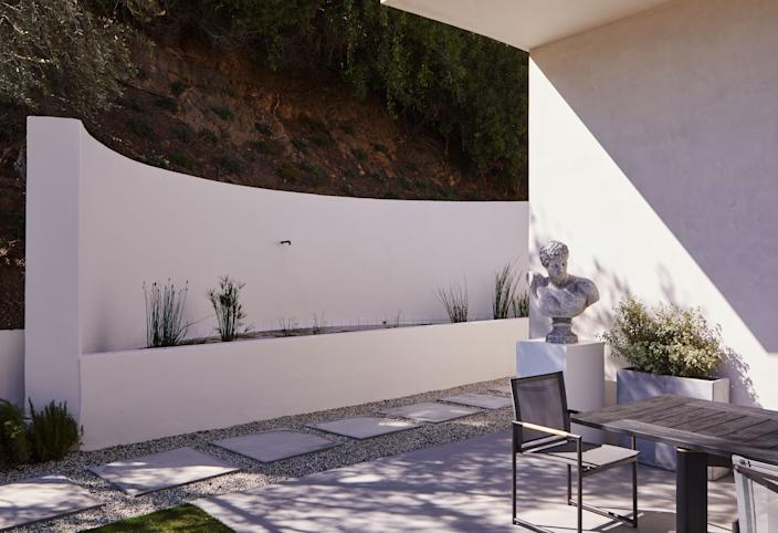 """<div class=""""caption""""> In this exterior area, adorned with a cast concrete sculpture of a man placed on a custom white pedestal, the Sonoma forge rustic nickel spout is from <a href=""""https://www.euroconcepts.com/"""" rel=""""nofollow noopener"""" target=""""_blank"""" data-ylk=""""slk:EuroConcepts"""" class=""""link rapid-noclick-resp"""">EuroConcepts</a> and the Ora dining table and chairs are from <a href=""""https://www.harbouroutdoor.com/"""" rel=""""nofollow noopener"""" target=""""_blank"""" data-ylk=""""slk:Harbour Outdoor"""" class=""""link rapid-noclick-resp"""">Harbour Outdoor</a>. </div>"""