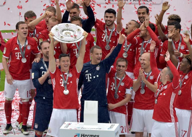 Bayern Munich's Robert Lewandowski holds the trophy as he and team celebrate winning their Bundesliga title, in Munich, on May 14, 2016