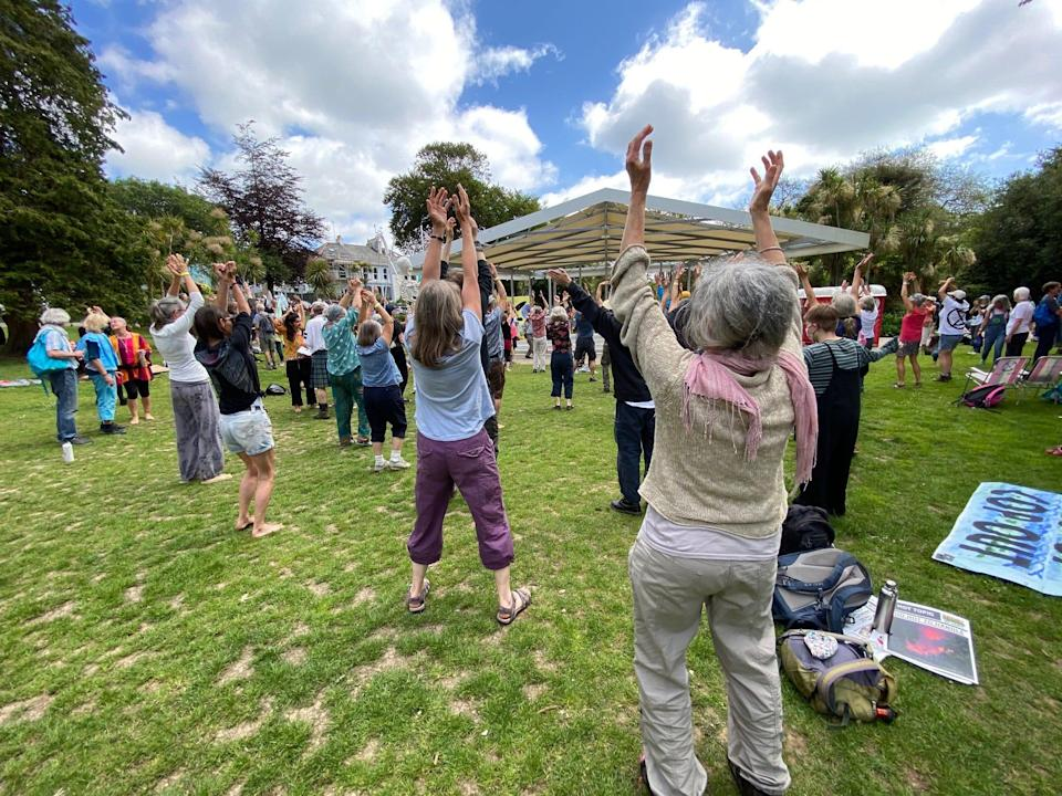 Activists gather in Kimberley Park, in Falmouth, England, on June 12, 2021, as they rehearse for a protest march involving a dance routine.