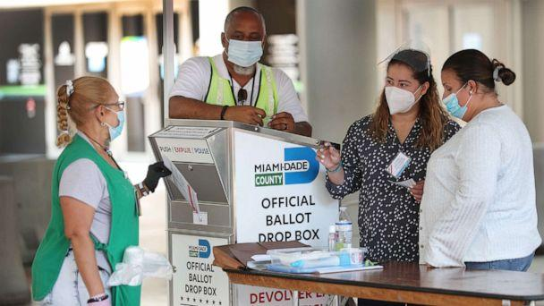 PHOTO: Poll workers help a voter put their mail-in ballot in an official Miami-Dade County ballot drop box on Aug. 11, 2020, in Miami. (Joe Raedle/Getty Images)