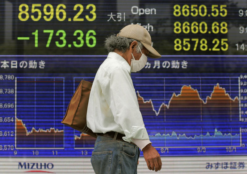 A man walks in front of the electronic stock board of a securities firm showing Japan's Nikkei 225 index falling 173.36 points to 8596.23 in Tokyo, Wednesday, Oct. 10, 2012. Worries about Europe's debt crisis, signs of weak global growth and expectations of lower U.S. corporate earnings sent most Asian stock markets down Wednesday. (AP Photo/Itsuo Inouye)