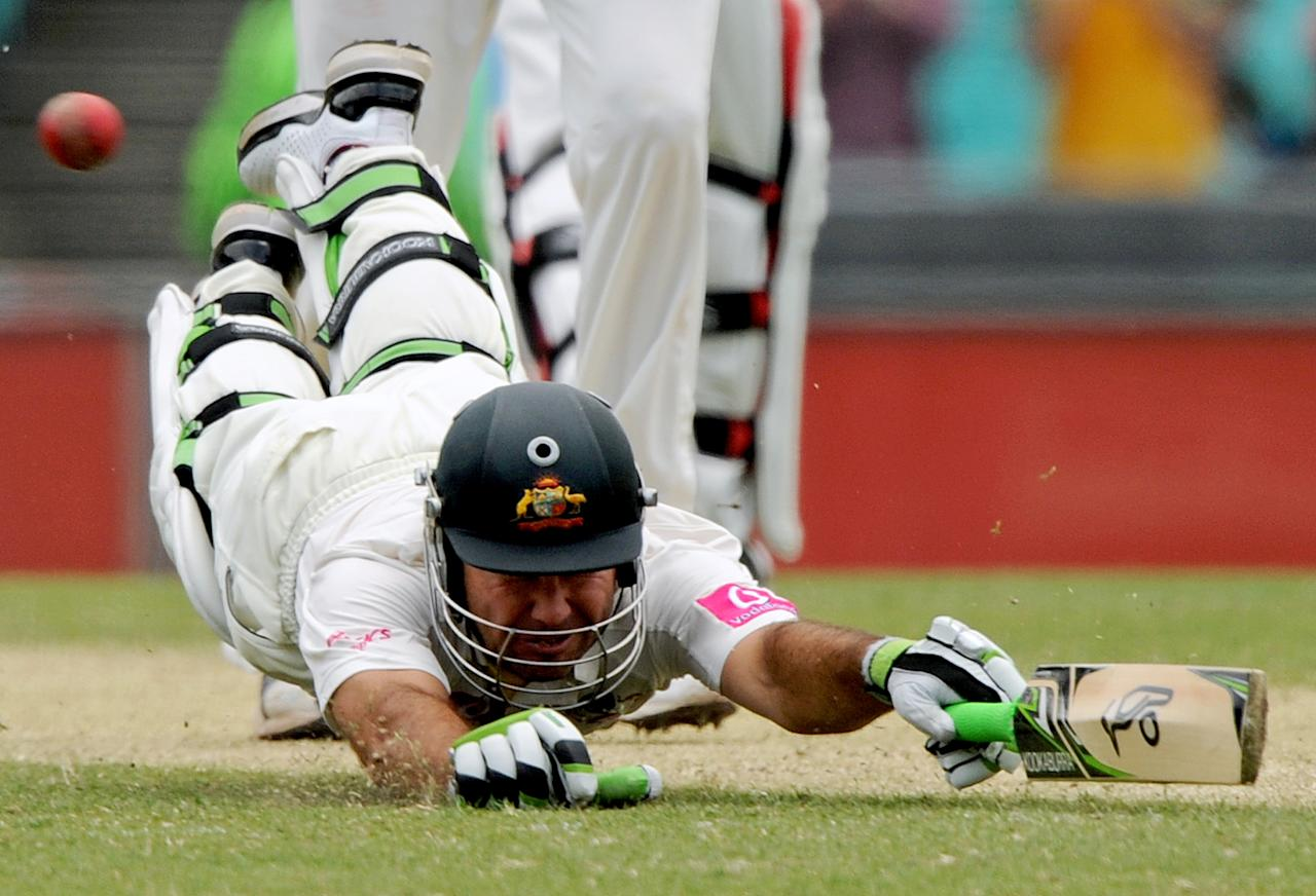 Australian batsman Ricky Ponting dives to make his ground and score a run to reach his 100 on day two of the second cricket test against India at the Sydney Cricket Ground on January 4, 2012. RESTRICTED TO EDITORIAL USE - STRICTLY NO COMMERCIAL USE  TOPSHOTS  AFP PHOTO / Greg WOOD (Photo credit should read GREG WOOD/AFP/Getty Images)