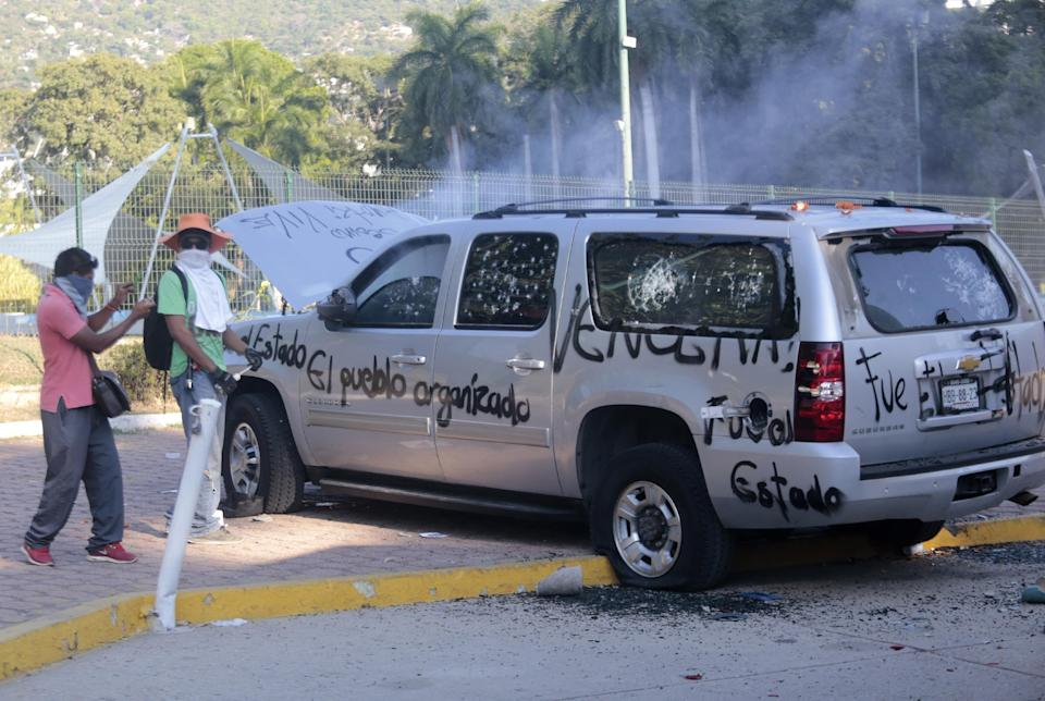 Protesters attack the car of Mayor Luis Walton during a rally by classmates and relatives of the 43 missing students in Acapulco, Guerrero State, Mexico on December 19, 2014 (AFP Photo/Pedro Pardo)
