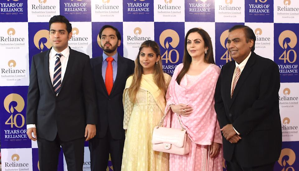 India's richest man and oil-to-telecom conglomerate Reliance Industries chairman Mukesh Ambani (R) and his wife Nita Ambani (2R) pose with their children (L-C) Akash Ambani, Anant Ambani and Isha Ambani as they arrive for the company's 40th AGM in Mumbai on July 21, 2017.  Indian oil-to-telecom conglomerate Reliance Industries' first-quarter consolidated profit jumped 28 percent July 20, pumped up by higher margins from its core oil refining business, the group said, beating analyst estimates.  / AFP PHOTO / INDRANIL MUKHERJEE        (Photo credit should read INDRANIL MUKHERJEE/AFP via Getty Images)