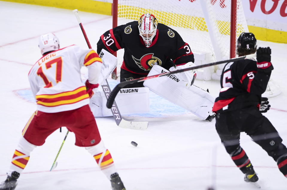 Calgary Flames left wing Milan Lucic (17) moves in on Ottawa Senators goaltender Matt Murray (30) as Senators defenceman Mike Reilly (5) gets his stick twisted up behind him during second period NHL hockey action in Ottawa on Monday, March 1, 2021. (Sean Kilpatrick/The Canadian Press via AP)