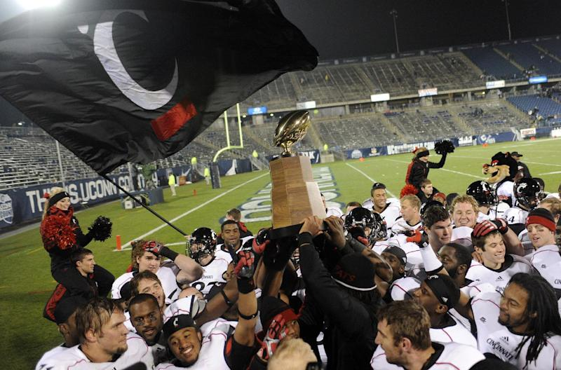 FILE - In this Dec. 1, 2012, file photo, Cincinnati holds up the Big East Championship trophy after earning a the share of the title when they defeated Connecticut 34-17 in an NCAA college football game at Rentschler Field in East Hartford, Conn. The soon-to-be-former Big East made one big component on Tuesday, announcing its broadcasting deal with ESPN. Now it still needs a new name. The renamed league will include South Florida, Connecticut, Cincinnati, Temple, Memphis, Central Florida, SMU and Houston in 2013. East Carolina and Tulane are to join in 2014 and Navy is scheduled for football in 2015. (AP Photo/Jessica Hill, File)