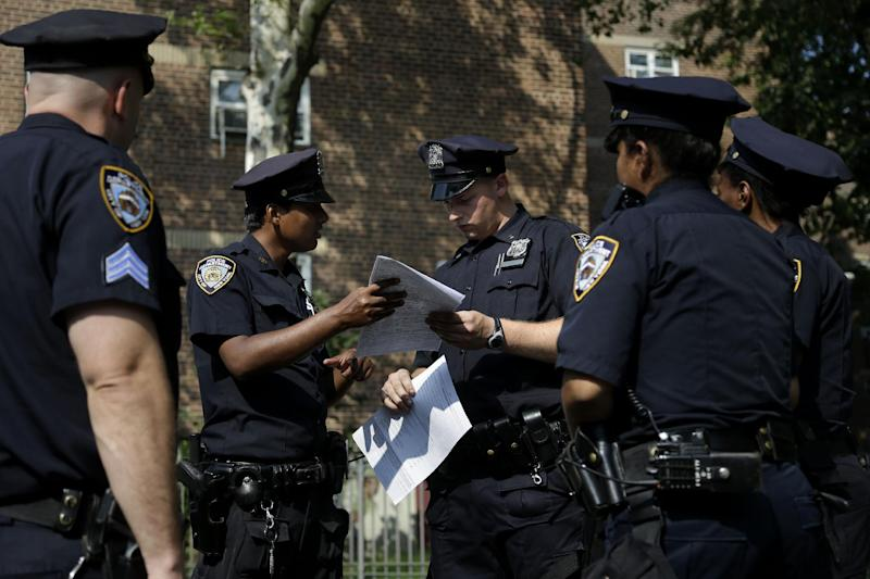 FILE - In this Aug. 13, 2013 file photo, police officers take a report from a woman who had her phone stolen in the Brownsville section of Brooklyn, New York. A federal appeals court on Thursday, Oct. 31, 2013, blocked a judge's order requiring changes to the New York Police Department's stop-and-frisk program and removed the judge from the case. (AP Photo/Seth Wenig, File)